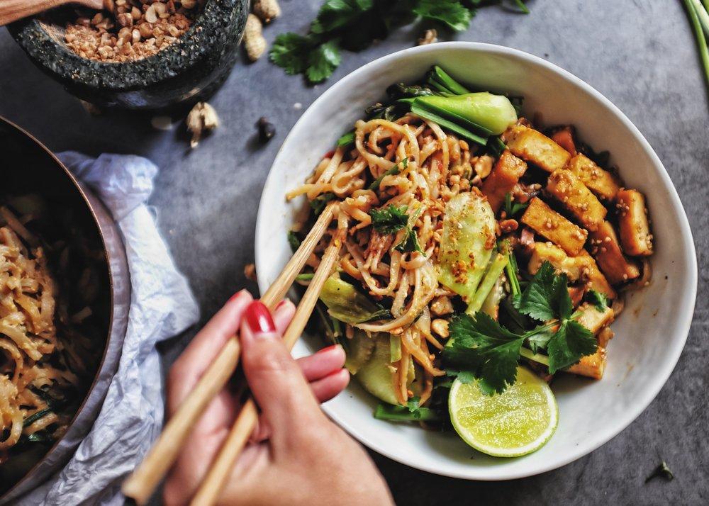 Udon avec sauce Padthai, menu végétarien / végétalien sain; Nouilles Padthai avec tofu fumant et légumes mélangés - Bok Choy chinois pour bébé, ciboulette à l'ail, échalote et garniture aux arachides écrasées. tenir les baguettes.