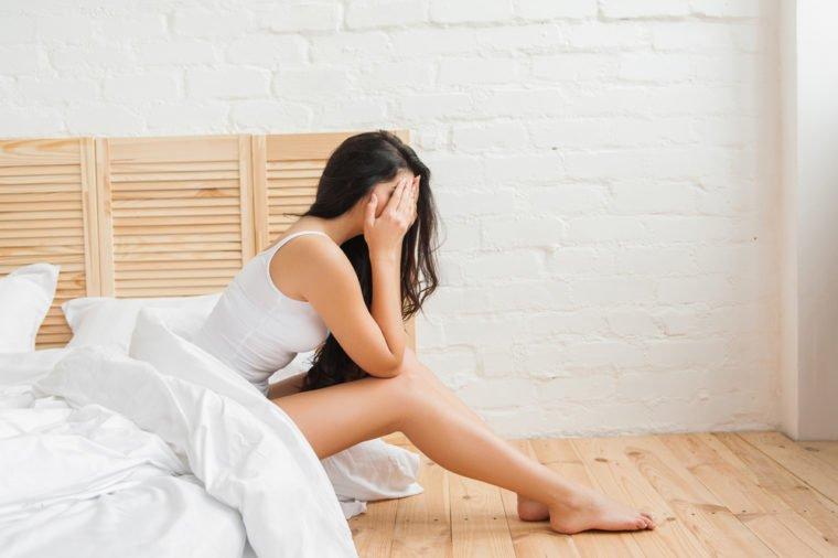 femme couvrant son visage avec les mains assis dans son lit
