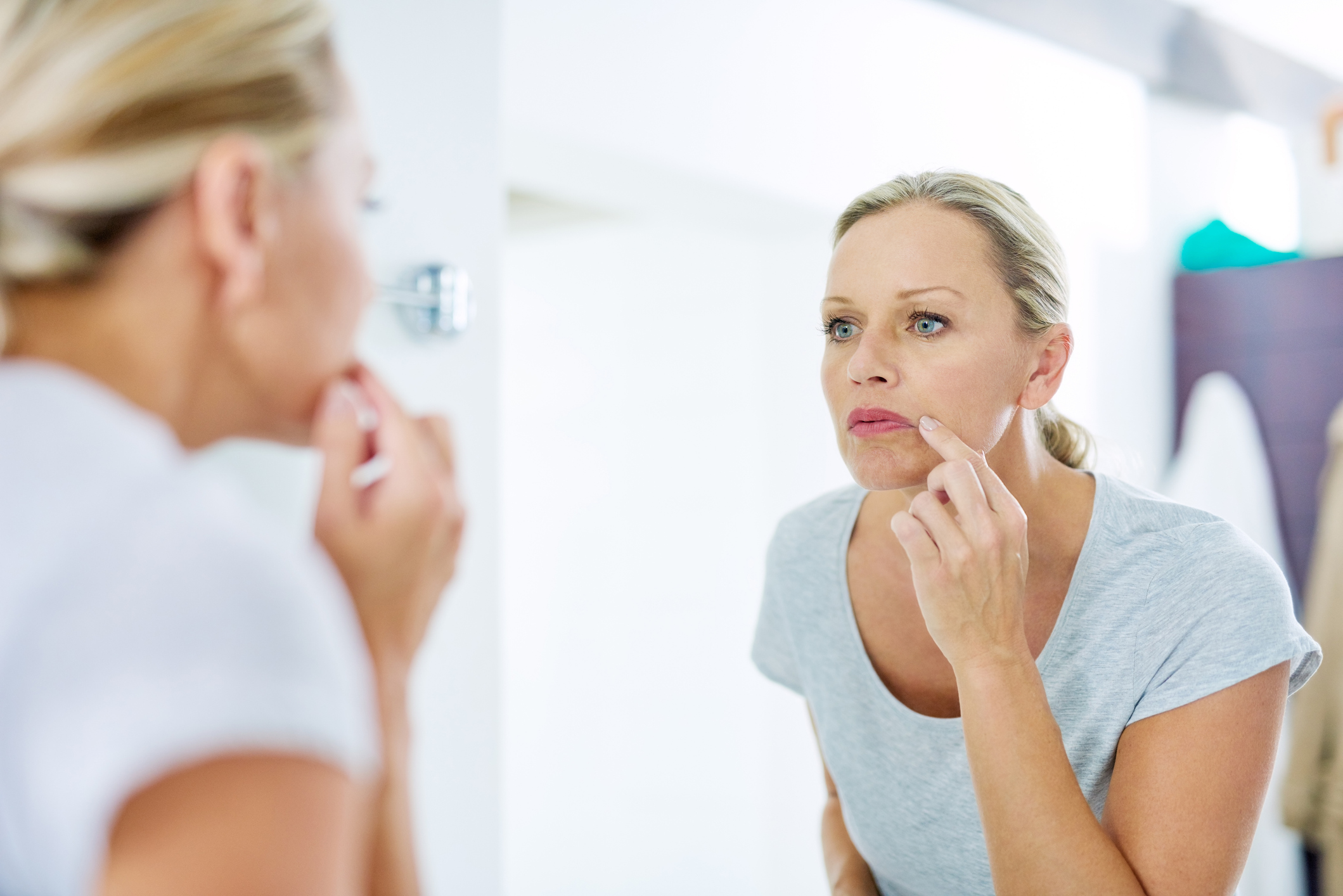 femme regardant sa peau dans le miroir