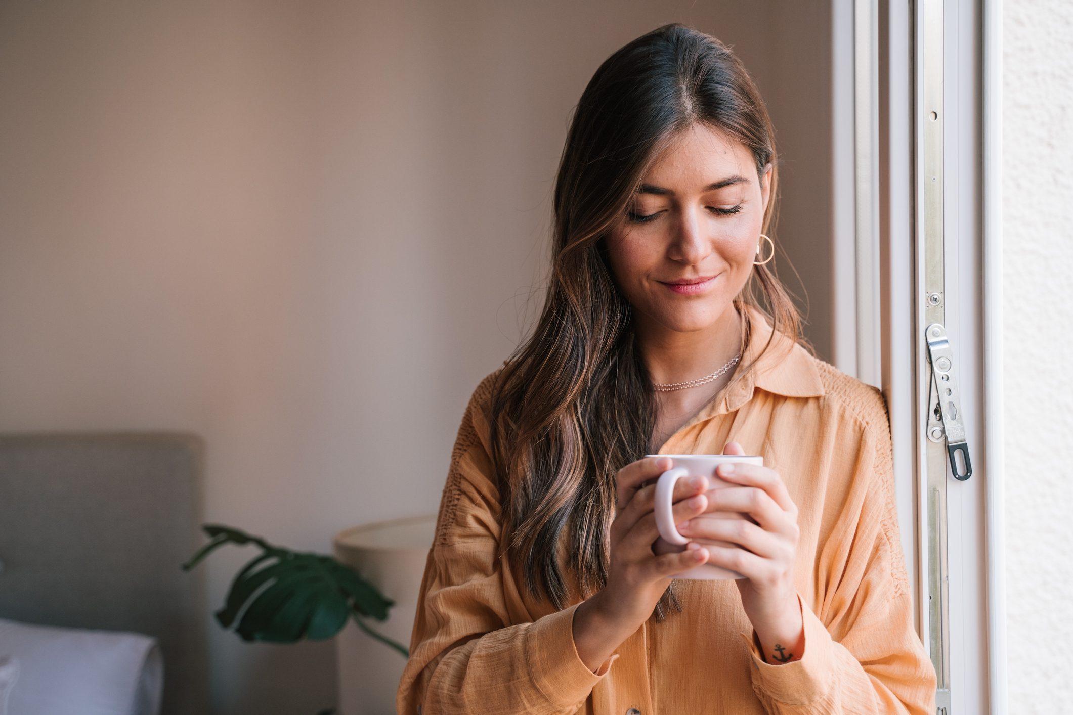 Jeune femme, à, tasse café, par, fenêtre, chez soi